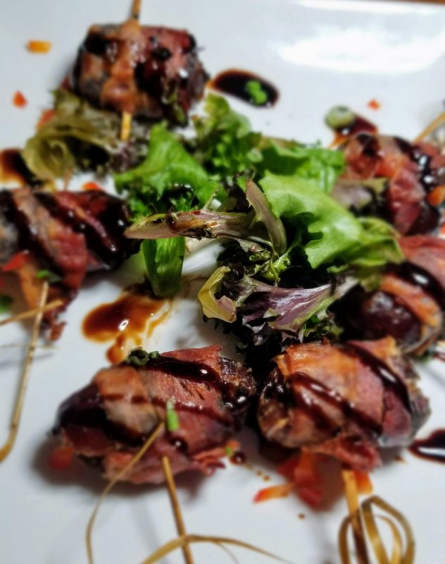 Bacon-wrapped Stuffed Dates stuffed with feta cheese and drizzled with fig balsamic reduction